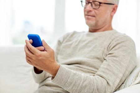 Photo pour close up of senior man with smartphone at home - image libre de droit