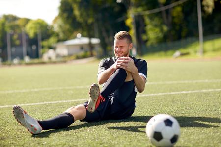Foto de injured soccer player with ball on football field - Imagen libre de derechos