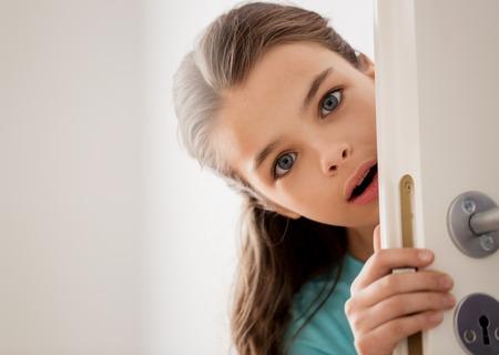 scared beautiful girl hiding behind door at home