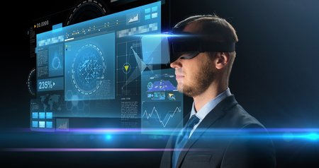 Foto de technology, people, cyberspace and augmented reality concept - young businessman with virtual headset or 3d glasses and screen projection over black background - Imagen libre de derechos