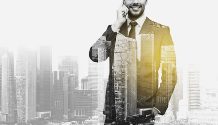 Photo pour business, technology and people concept - smiling businessman calling on smartphone over city buildings and double exposure effect - image libre de droit