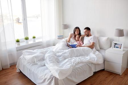 Foto de happy family reading book in bed at home - Imagen libre de derechos
