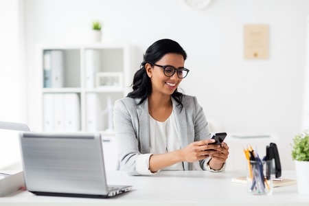 Photo pour business, technology, communication and people concept - happy smiling businesswoman with smartphone and laptop at office - image libre de droit