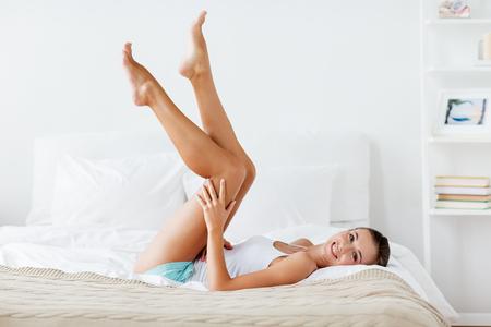 Foto de happy woman lying on bed and touching legs at home - Imagen libre de derechos