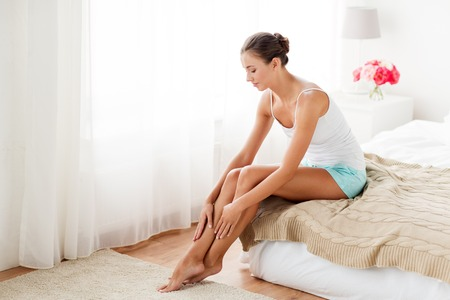 Photo pour people, beauty, depilation, epilation and bodycare concept - beautiful woman touching smooth leg skin on bed at home bedroom - image libre de droit