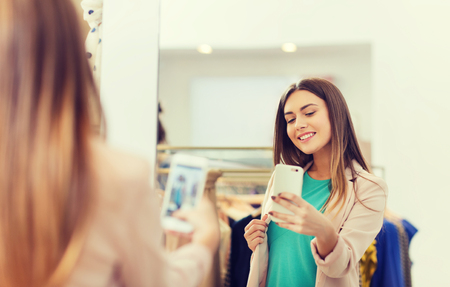 Photo pour woman taking mirror selfie by smartphone at store - image libre de droit