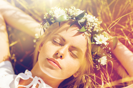 Photo pour happy woman in wreath of flowers lying on straw - image libre de droit