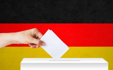 hand of german with ballot and box on election
