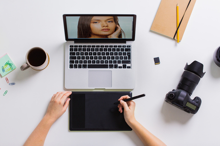 Photo pour woman with camera working on laptop at table - image libre de droit