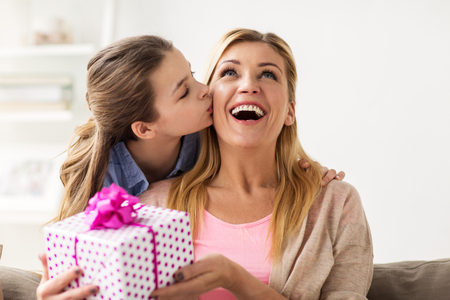 Photo for people, holidays and family concept - happy girl giving birthday present to mother at home - Royalty Free Image