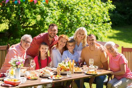 Foto de leisure, holidays and people concept - happy family having festive dinner or summer garden party - Imagen libre de derechos