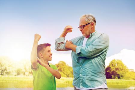Foto de happy grandfather and grandson showing muscles - Imagen libre de derechos