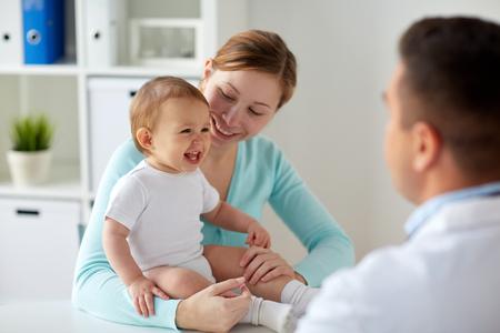 Foto de happy woman with baby and doctor at clinic - Imagen libre de derechos