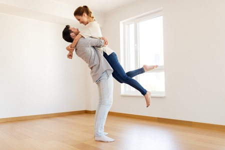 happy couple at empty room of new home
