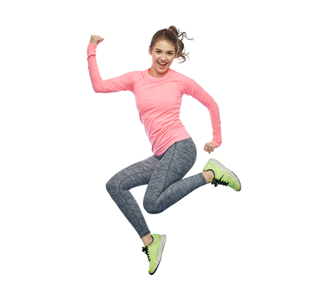 Foto de happy smiling sporty young woman jumping in air - Imagen libre de derechos