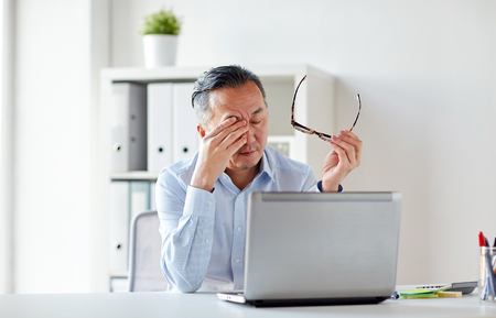 Photo pour tired businessman with glasses at laptop in office - image libre de droit