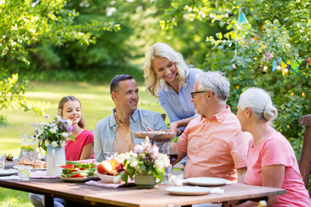 Foto de happy family having dinner or summer garden party - Imagen libre de derechos