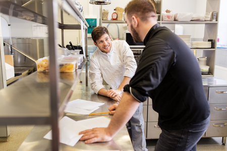 Photo pour cooking food, profession and people concept - happy male chef and cook with grocery lists or bills at restaurant kitchen - image libre de droit