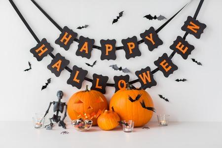Photo pour carved pumpkins with candies and halloween garland - image libre de droit
