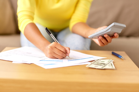 business, finances and people concept - woman with money, papers and calculator at home