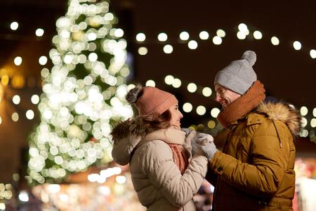 Foto de winter holidays and people concept - happy young couple dating at christmas tree in evening - Imagen libre de derechos