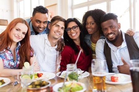 Photo pour happy friends eating at restaurant - image libre de droit