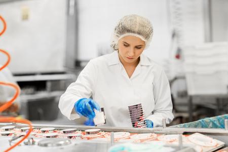Photo pour woman working at ice cream factory conveyor - image libre de droit