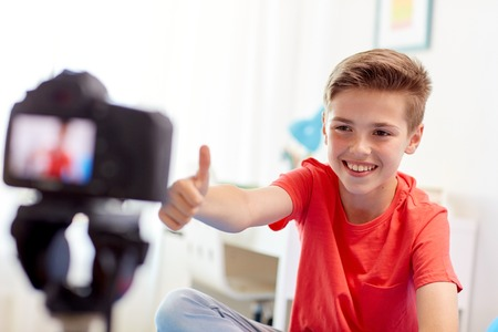 Photo for happy boy with camera recording video at home - Royalty Free Image