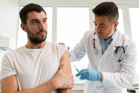 Photo pour patient and doctor with syringe doing vaccination - image libre de droit