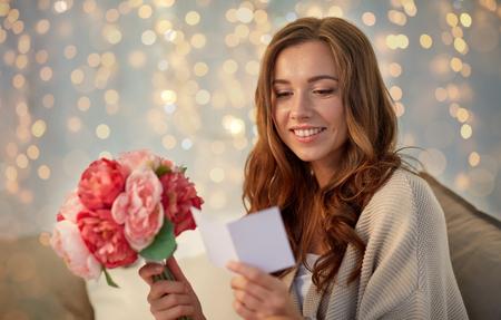 Foto de happy woman with flowers and greeting card at home - Imagen libre de derechos