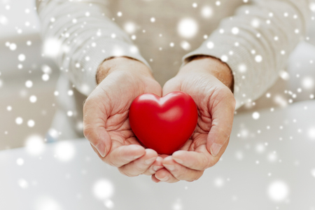 Photo pour close up of senior man with red heart in hands - image libre de droit
