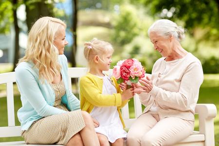 Photo pour happy family giving flowers to grandmother at park - image libre de droit