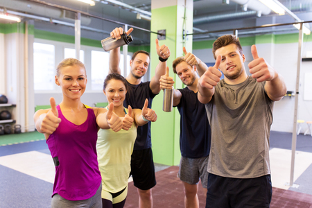 Photo for group of happy friends in gym showing thumbs up - Royalty Free Image