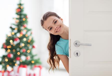 Photo pour happy smiling beautiful girl behind door at home - image libre de droit