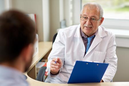 Photo pour senior doctor talking to male patient at hospital - image libre de droit