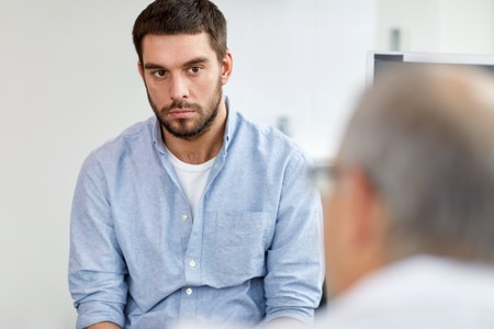 Photo pour young male patient talking to doctor at hospital - image libre de droit