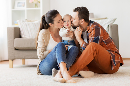 Photo pour happy mother and father kissing baby at home - image libre de droit