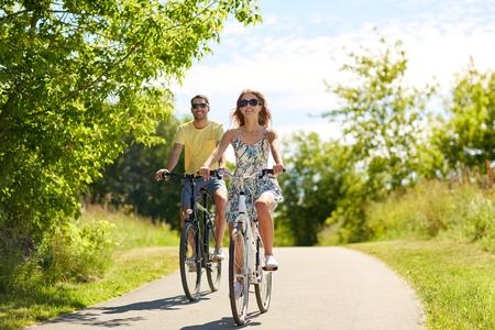 Foto de happy young couple riding bicycles in summer - Imagen libre de derechos