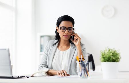 Photo pour businesswoman calling on smartphone at office - image libre de droit