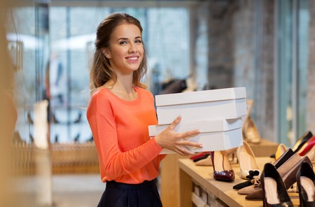 woman or shop assistant with shoe boxes at store