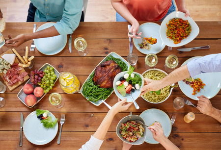 Foto de thanksgiving day, eating and leisure concept - group of people having dinner at table with food - Imagen libre de derechos
