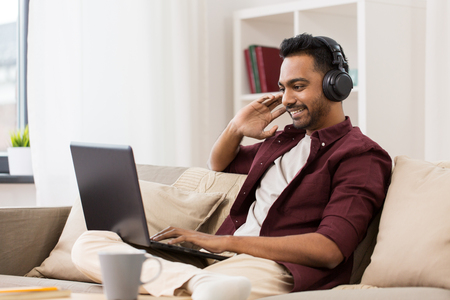 Foto de technology, leisure and people concept - happy man in wireless headphones with laptop computer listening to music at home - Imagen libre de derechos