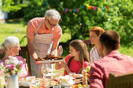 Foto de leisure, holidays and people concept - happy family having festive dinner or barbecue party at summer garden - Imagen libre de derechos
