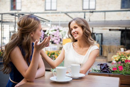 Foto de happy young women drinking coffee at outdoor cafe - Imagen libre de derechos