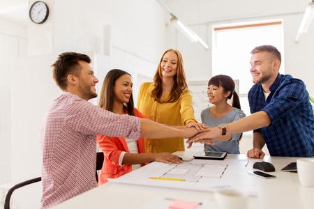 Photo pour creative team holding hands together at office - image libre de droit