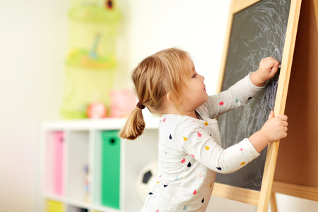 Foto de happy little girl drawing on chalk board at home - Imagen libre de derechos