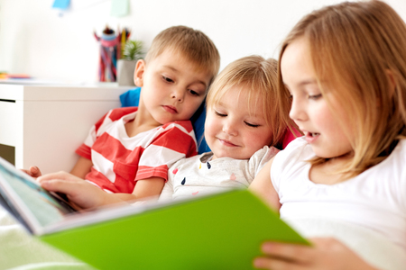 Photo for little kids reading book in bed at home - Royalty Free Image