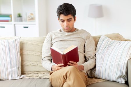 Foto de man sitting on sofa and reading book at home - Imagen libre de derechos