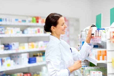 Photo pour happy female apothecary with drug at pharmacy - image libre de droit