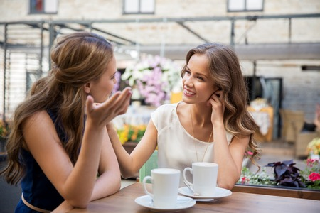 Photo pour happy young women drinking coffee at outdoor cafe - image libre de droit